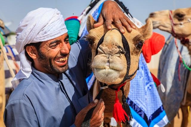 Dubai: Camel handler with his animal at Dubai Camel Racing Club